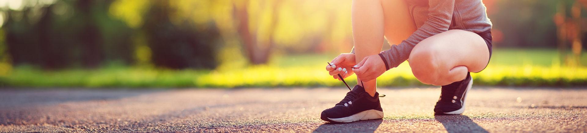 Elle lace ses baskets sur une route en nature
